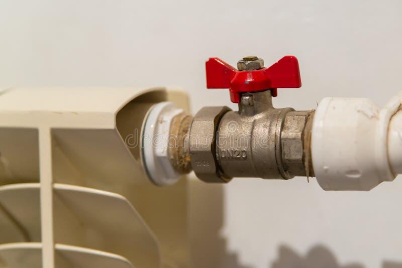 Válvula del agua con la manija roja vávula de bola usada en sistemas de la fontanería y de calefacción Colocaciones de la fontane imagen de archivo