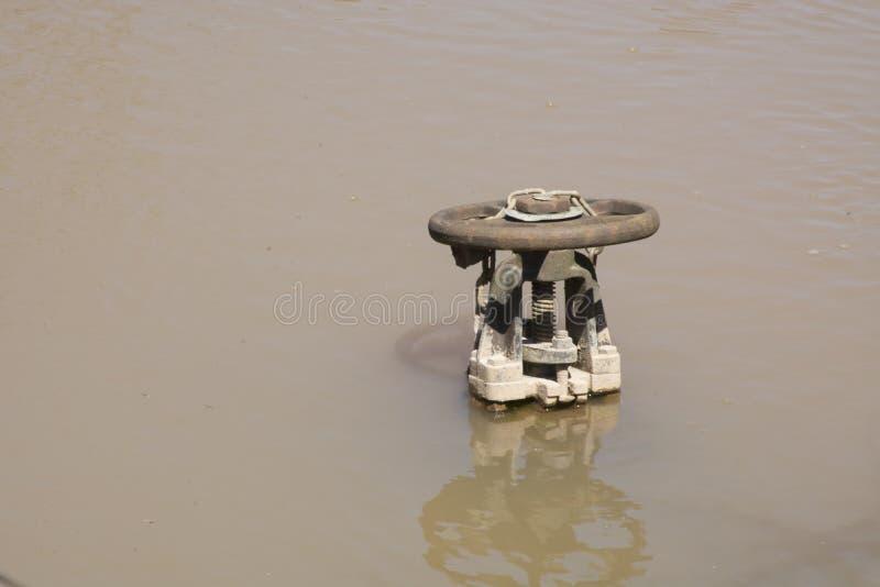 Válvula del agua en una charca imagen de archivo