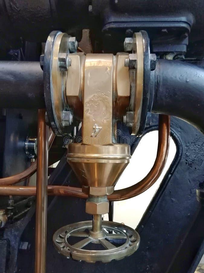 Válvula industrial de cobre amarillo vieja grande con la manija redonda montada en una máquina negra grande con los pernos y los  fotografía de archivo