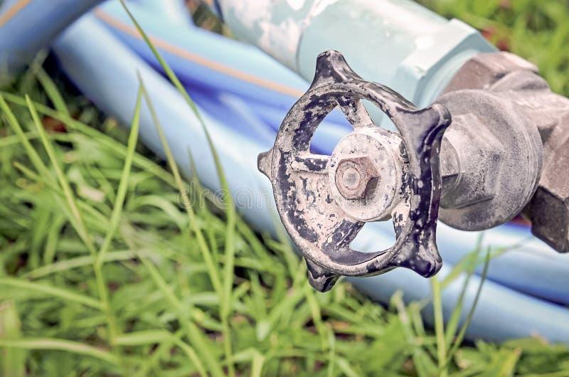 Válvula velha da água com a mangueira de borracha azul da água fotografia de stock