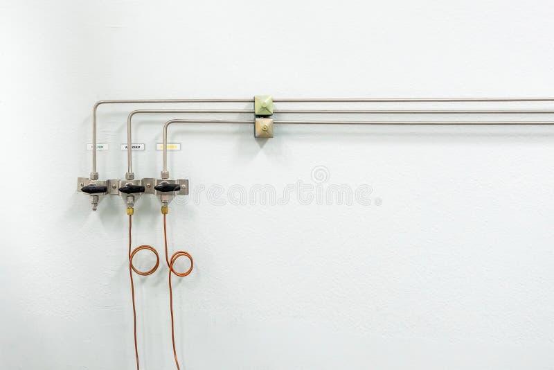 Válvulas del nitrógeno, del helio, de los tubos del aire del oxígeno y del metro cero de la presión de gas con el regulador para  fotos de archivo