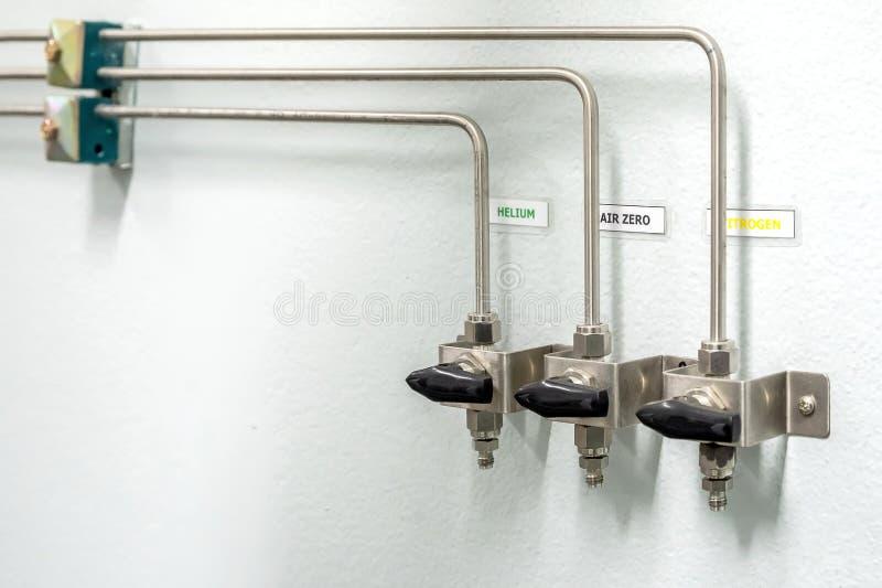 Válvulas del nitrógeno, del helio, de los tubos del aire del oxígeno y del metro cero de la presión de gas con el regulador para  fotografía de archivo