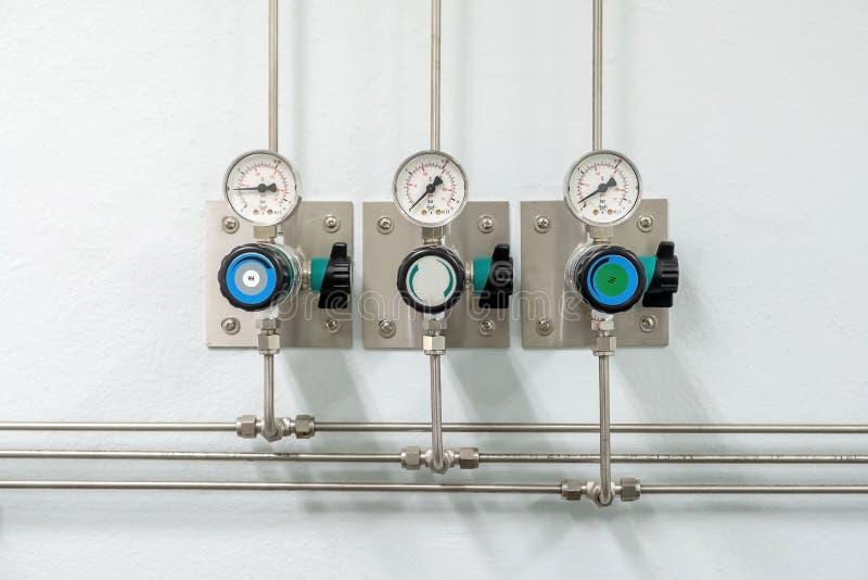 Válvulas del nitrógeno, del helio, de los tubos del aire del oxígeno y del metro cero de la presión de gas con el regulador para  imágenes de archivo libres de regalías