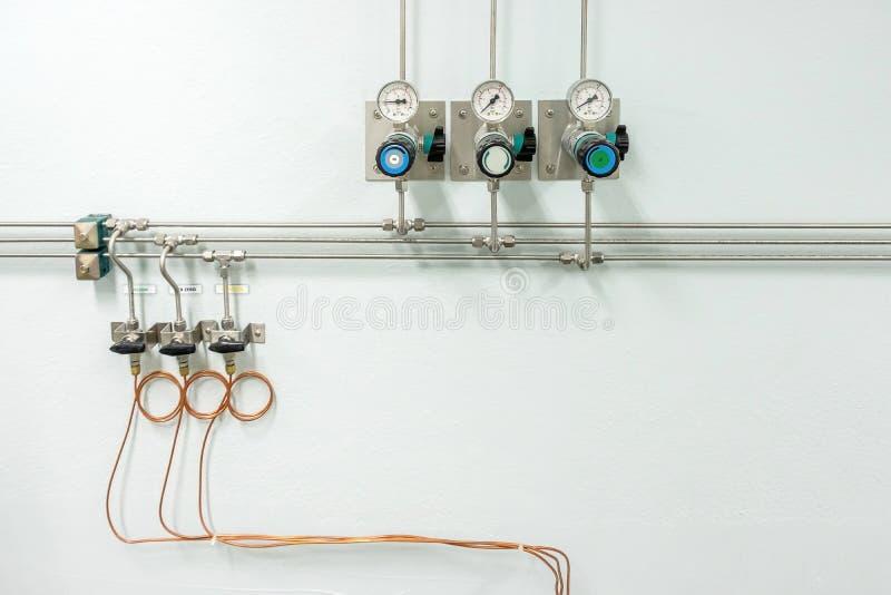 Válvulas del nitrógeno, del helio, de los tubos del aire del oxígeno y del metro cero de la presión de gas con el regulador para  imagen de archivo