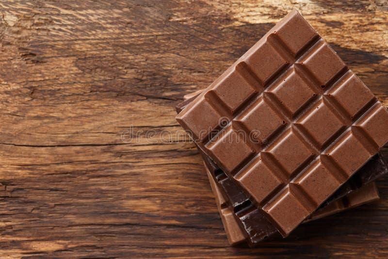 Vária pilha das barras de chocolate no fundo de madeira fotografia de stock royalty free