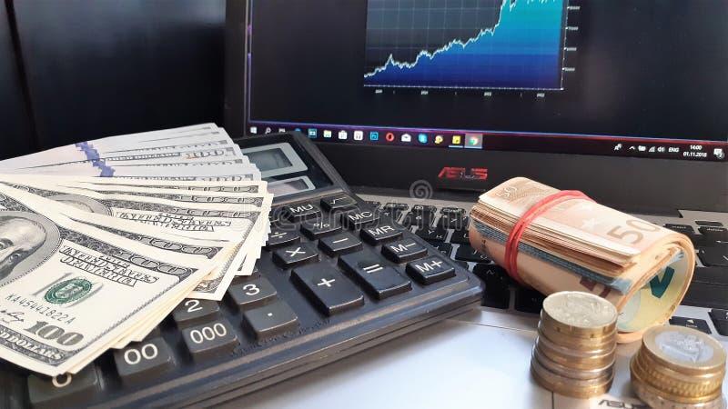 Várias cédulas do papel moeda no fim da tabela acima Cálculos financeiros, dinheiro e hexagrams foto de stock