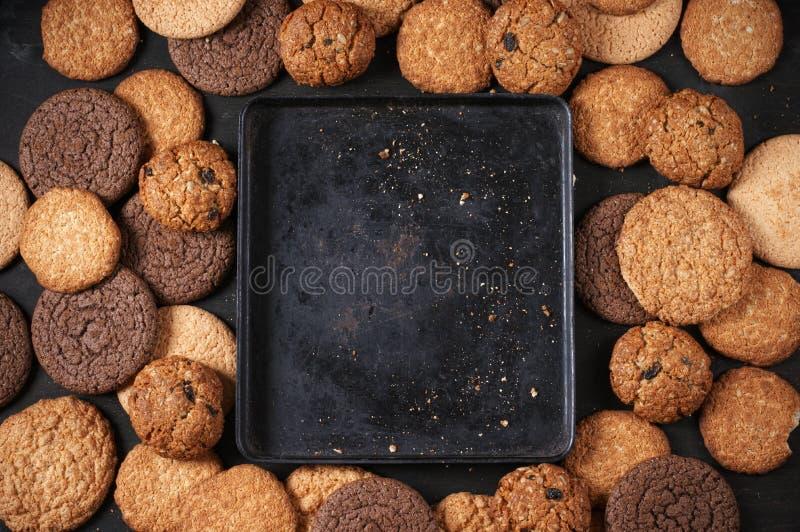 Várias cookies e bandeja de cozimento imagens de stock