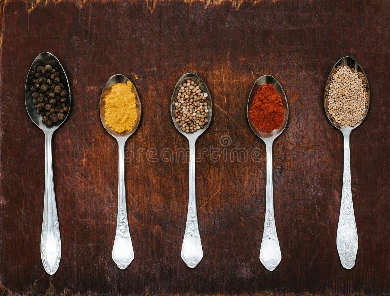 Várias ervas e especiarias coloridas para cozinhar no fundo escuro As ervas e as especiarias em um fundo de madeira imagem de stock royalty free