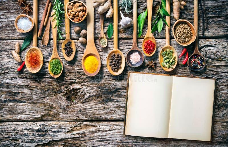 Várias ervas e especiarias para cozinhar na placa de madeira velha foto de stock royalty free