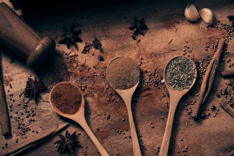 Várias especiarias e ervas coloridas mornas em colheres de madeira imagens de stock royalty free
