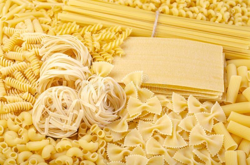 Várias formas e tipos de massas alimentícias italianas cruas secas, tais como penne, fusilli, farfalle, linguine, espaguete, fett fotografia de stock royalty free