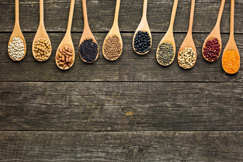 Várias leguminosa secadas em colheres de madeira imagem de stock