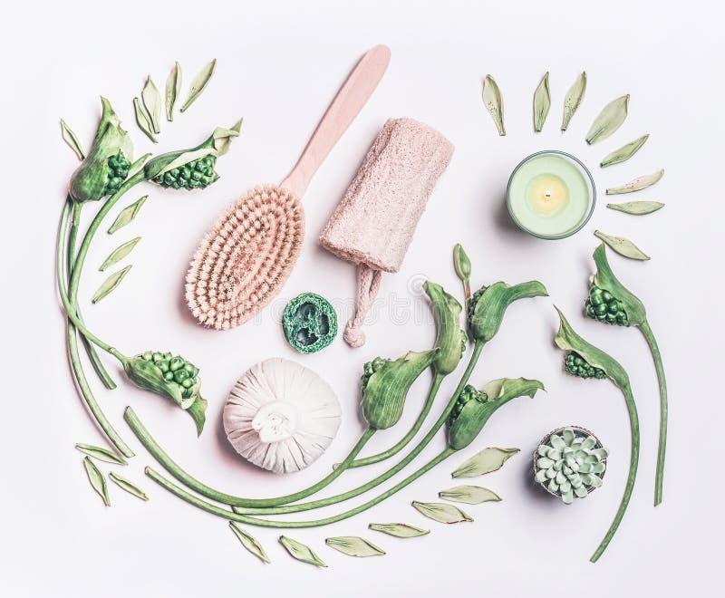 Vário equipamento das anti-celulites para a massagem seca em casa nas folhas da sagacidade branca do fundo e em flores verdes, vi foto de stock royalty free