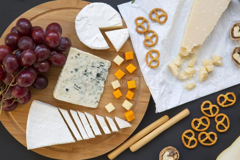 Vário queijo na placa redonda da placa de madeira com frutos, nozes, pretzeis e varas de pão no fundo escuro Configuração lisa fotografia de stock