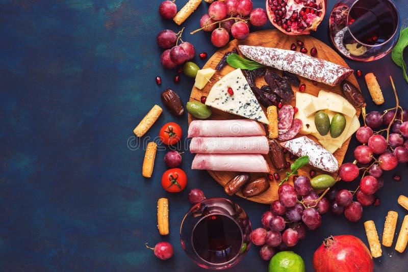 Vário vinho aperitivo-vermelho, frutos, salsichas, queijo, vegetais em um fundo escuro do finem Copie o espaço, vista superior imagens de stock