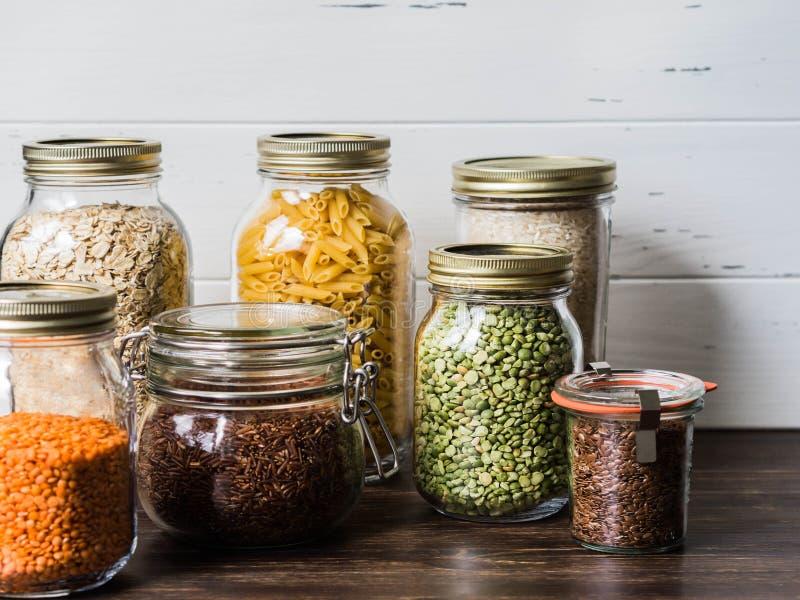 Vários cereais e sementes - o arroz, massa, farinha de aveia, linho, lentilhas, ervilhas verdes rachou nos frascos de vidro na ta fotos de stock royalty free