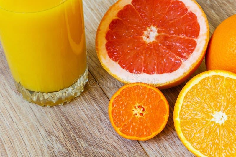 Vários citrinas e suco de laranja fotografia de stock