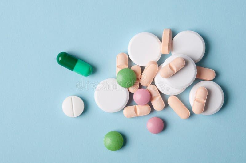Vários comprimidos e cápsulas da medicina, vista superior no fundo azul; as drogas seguras usam-se e o conceito do tratamento méd imagens de stock royalty free