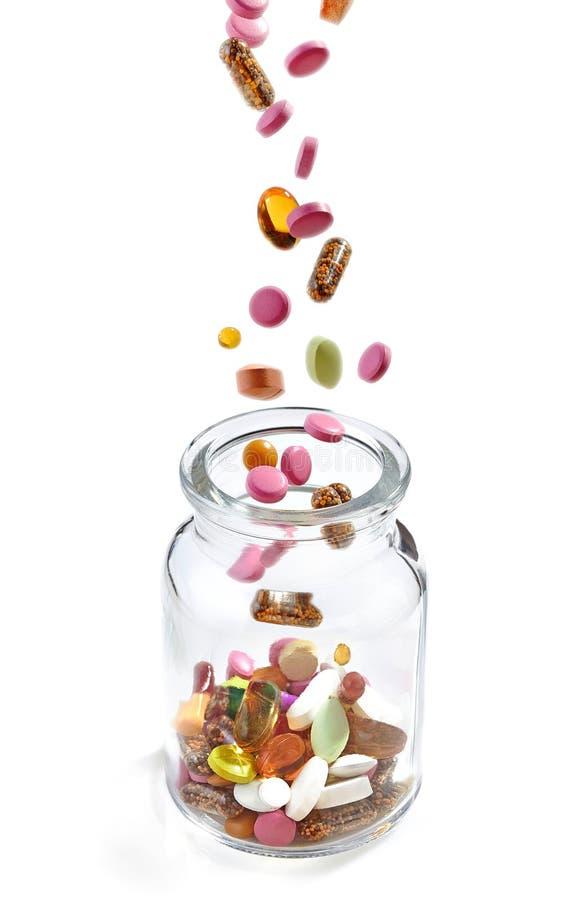Vários comprimidos médicos que caem no frasco foto de stock