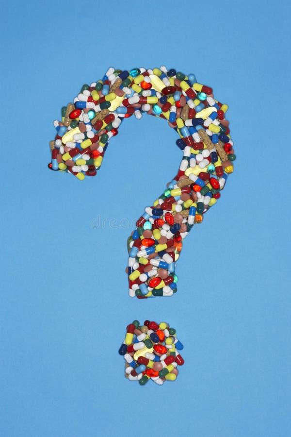 Vários comprimidos que formam o ponto de interrogação no fundo azul foto de stock royalty free