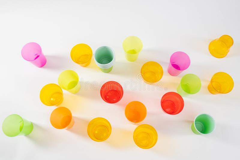 Vários copos plásticos brilhantes e coloridos que estão na superfície branca foto de stock