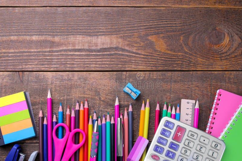 Vários escola e materiais de escritório coloridos em uma tabela de madeira marrom fotos de stock royalty free