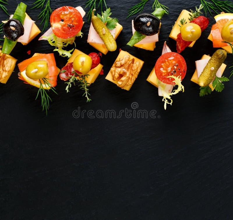 Vários espetos do queijo em um fundo preto imagens de stock royalty free
