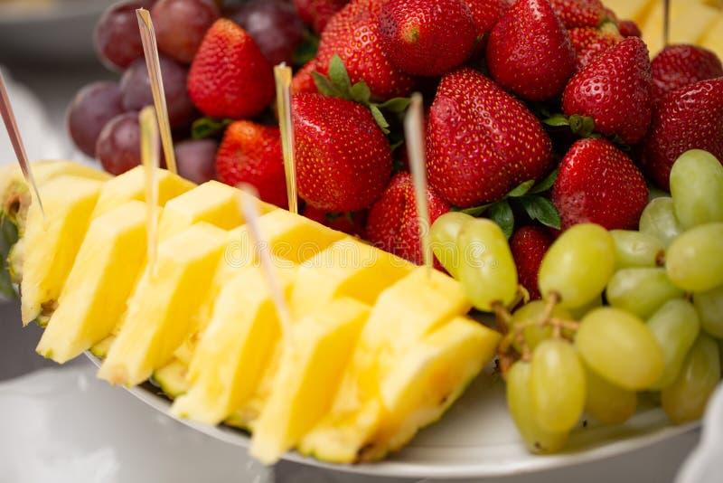 Vários frutos decorados na placa no restaurante, restauração do casamento Abacaxi, morango, uva verde foto de stock