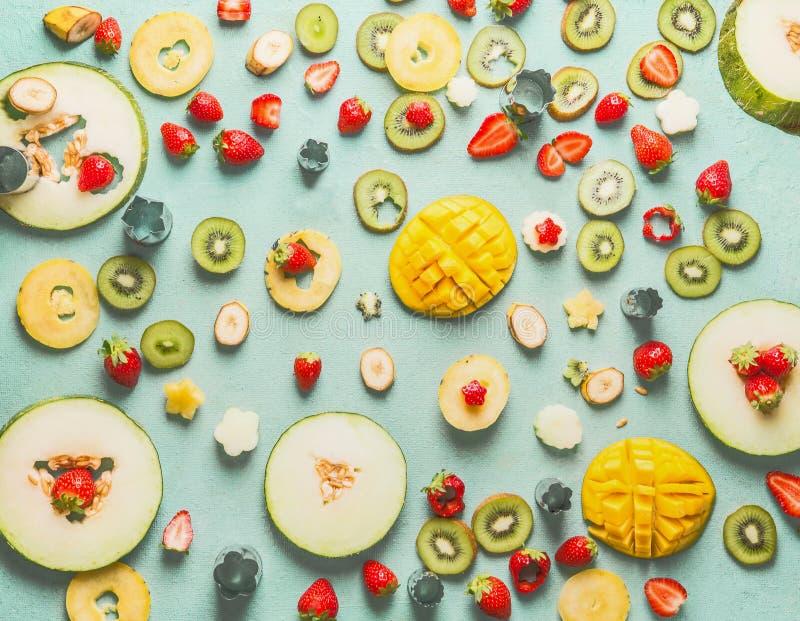 Vários frutos e bagas cortados na luz - fundo azul, vista superior, configuração do plano Alimento saudável do verão foto de stock royalty free