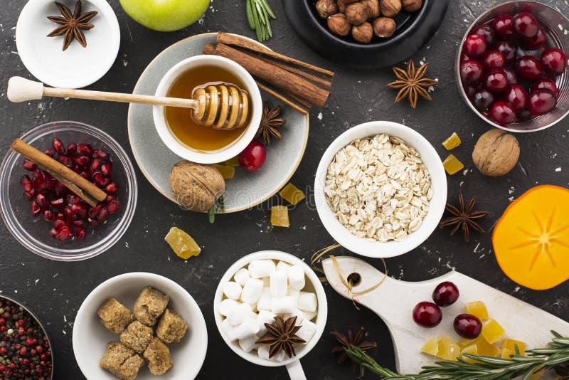 Vários ingredientes para o cozimento sazonal do inverno e as outras receitas, romã, mel, orezhi, maçãs, caquis, ervas foto de stock