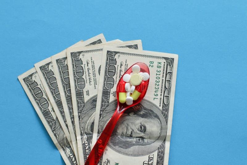 Vários medicinas e comprimidos na colher plástica com dinheiro fotografia de stock royalty free