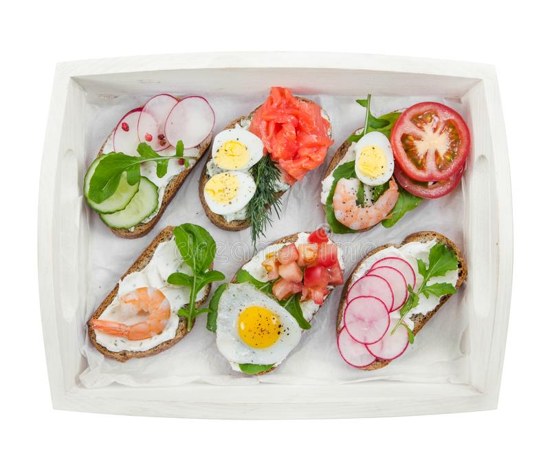 Vários mini sanduíches na bandeja de madeira branca isolada em b branco foto de stock royalty free