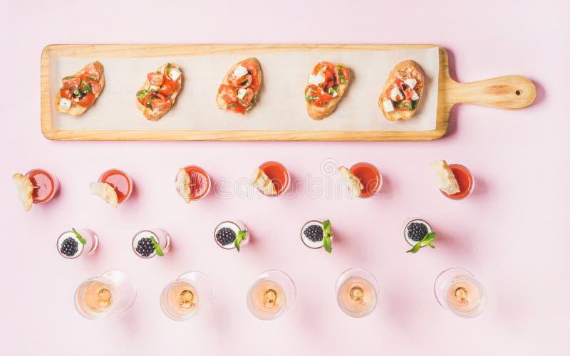 Vários petiscos, sanduíches do brushetta, tiros do gazpacho, sobremesas sobre o fundo cor-de-rosa fotografia de stock
