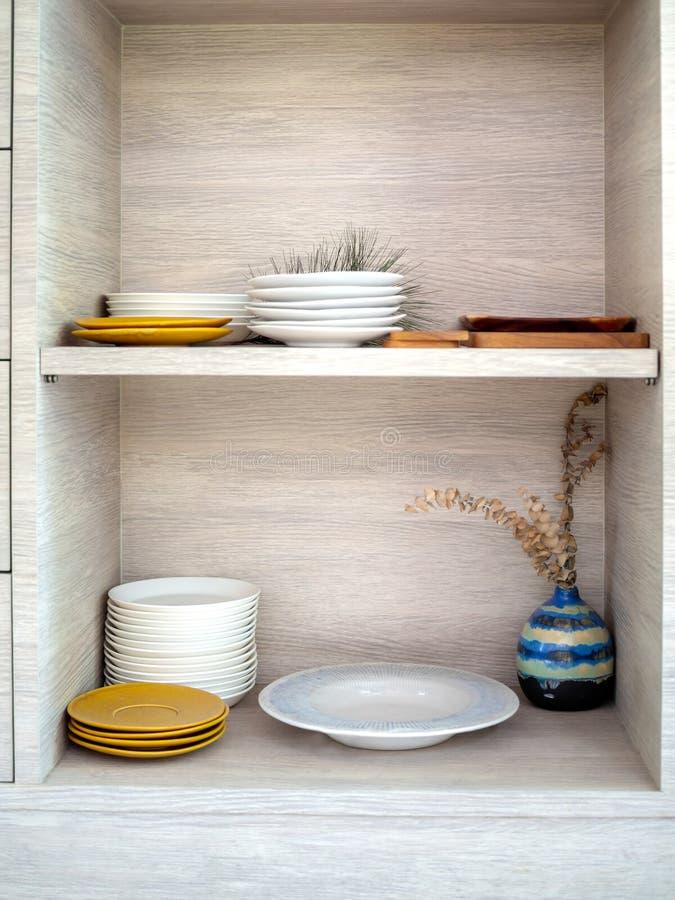 Vários pratos cerâmicos brancos e amarelos em ordem no armário de madeira fotografia de stock royalty free