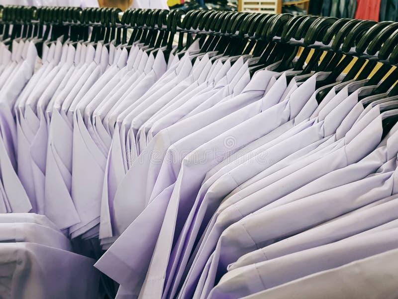 Vários tamanhos das camisas uniformes brancas com os ganchos na cremalheira curvada com foco seletivo foto de stock royalty free