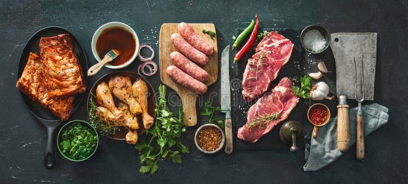 Vários tipos da grade e das carnes do BBQ com os utensílios da cozinha e do carniceiro do vintage fotos de stock