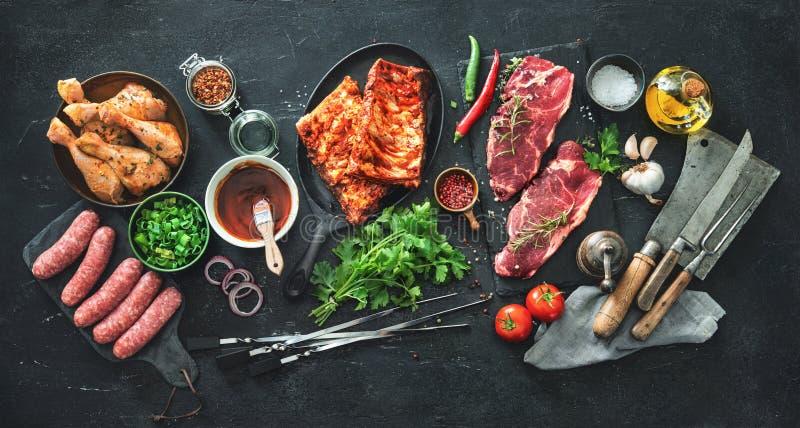 Vários tipos da grade e das carnes do BBQ com os utensílios da cozinha e do carniceiro do vintage imagens de stock