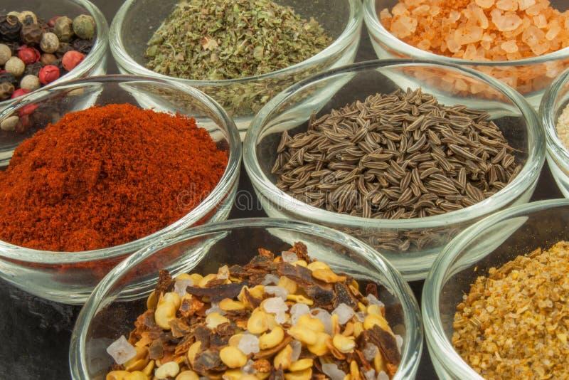Vários tipos das especiarias nas bacias de vidro em um fundo da ardósia Preparação para cozinhar o alimento picante Especiarias p fotografia de stock royalty free