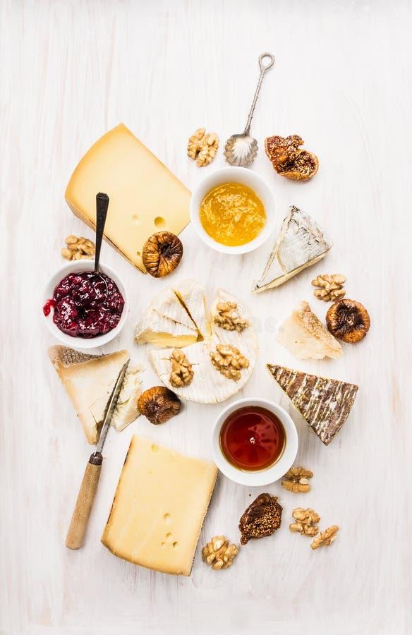 Vários tipos de queijo com molho, noz e figos imagens de stock