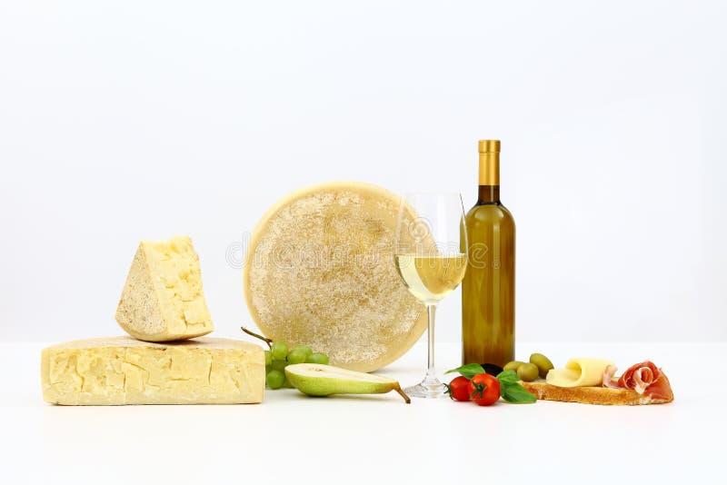 Vários tipos de queijo com vinho, tomates, manjericão, azeitonas, presunto, foto de stock