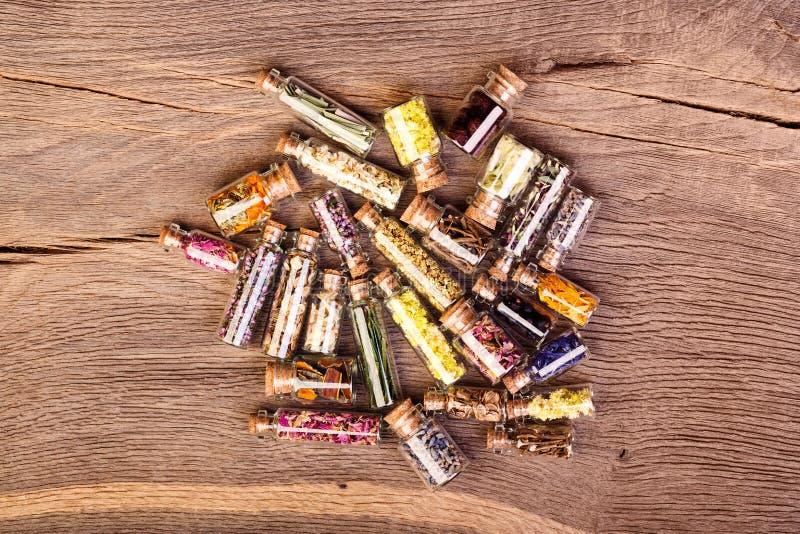 Vários tipos do chá e de ervas curas em umas garrafas de vidro claras sobre imagens de stock