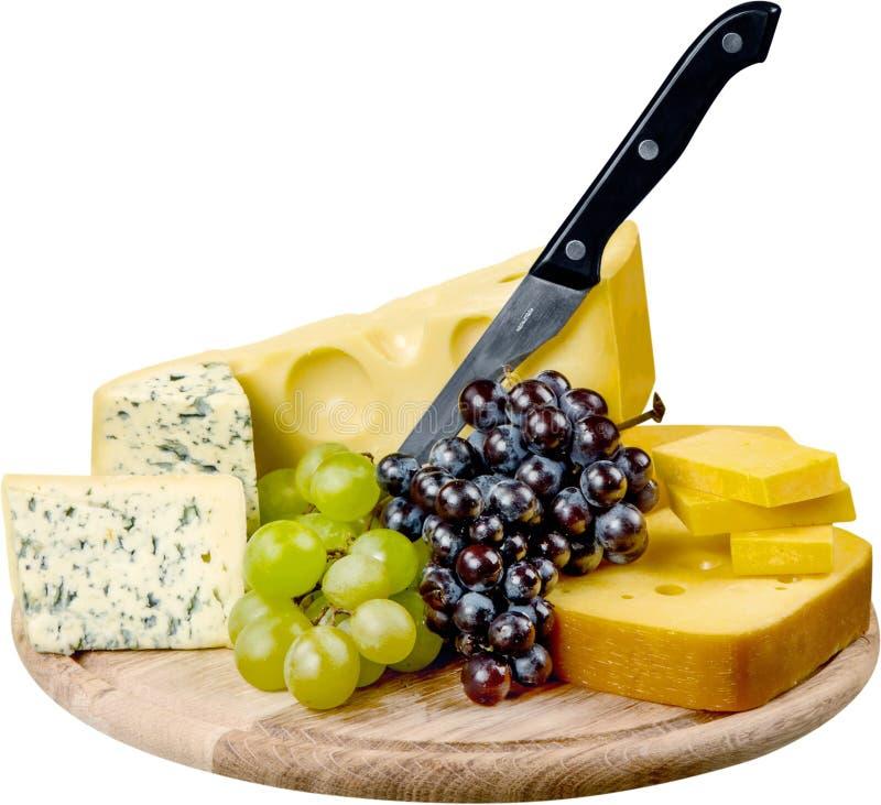 Vários tipos dos queijos, da uva, do pão e da faca imagem de stock