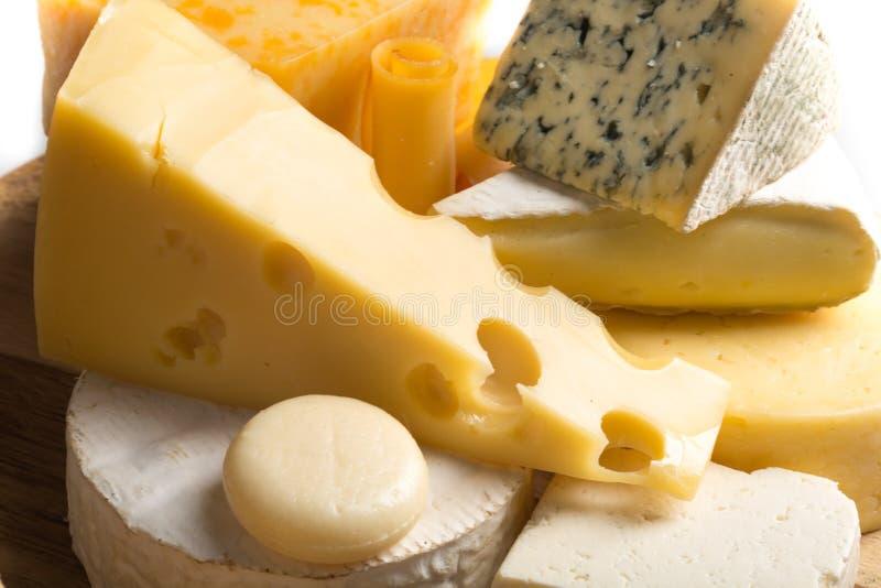Vários tipos dos queijos na bandeja de madeira - fotografia de stock