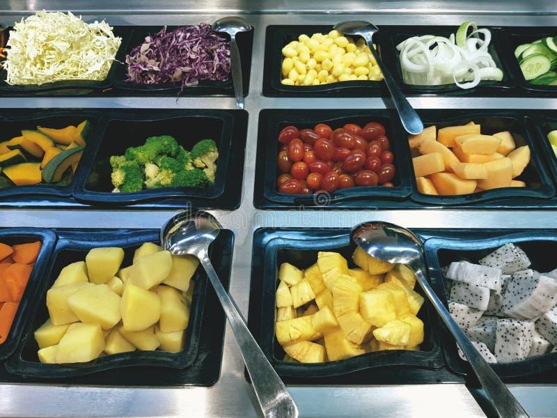 Vários tipos dos vegetais nas bandejas de barra de salada fotografia de stock royalty free