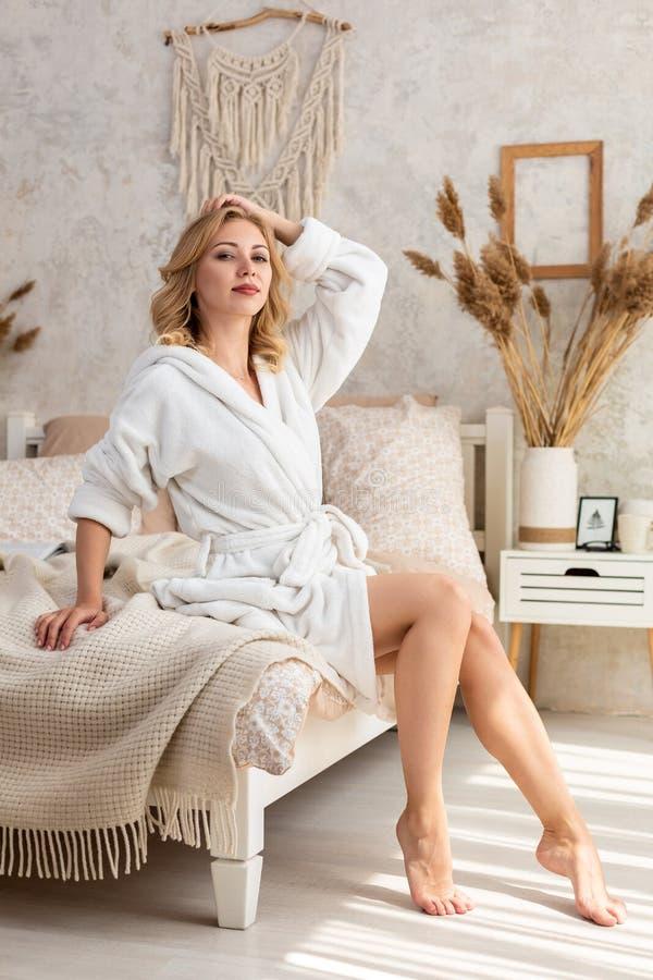 Väckt kvinnasammanträde på sängkanten som ut ser fönstret, kal fot på golvet Sidosikt av härligt royaltyfri foto