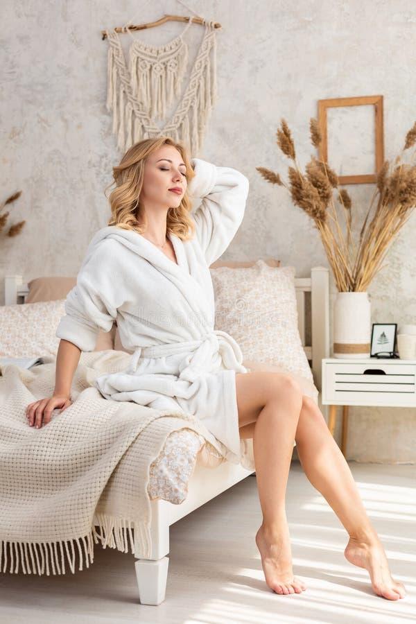 Väckt kvinnasammanträde på sängkanten som ut ser fönstret, kal fot på golvet Sidosikt av härligt royaltyfria bilder