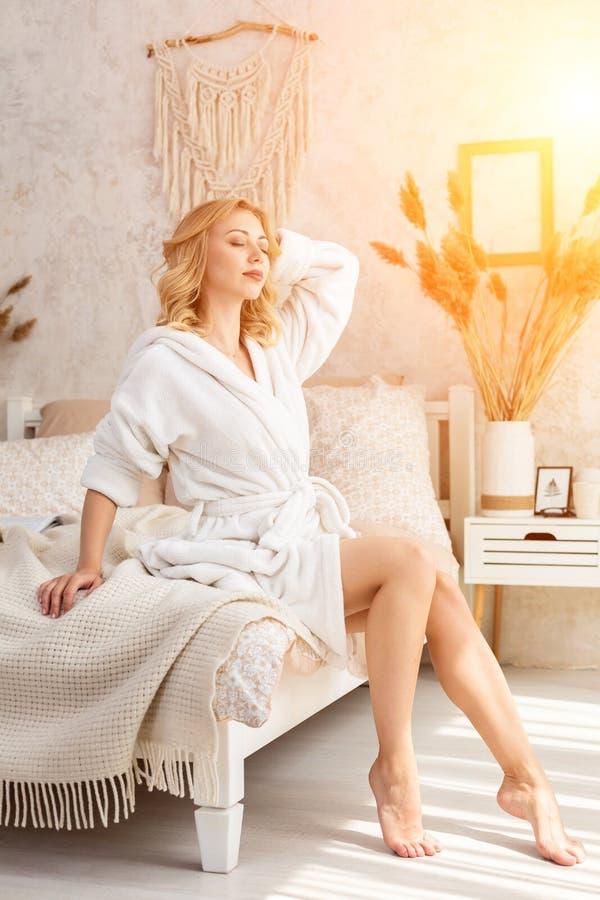 Väckt kvinnasammanträde på sängkanten som ut ser fönstret, kal fot på golvet Sidosikt av härligt arkivfoton