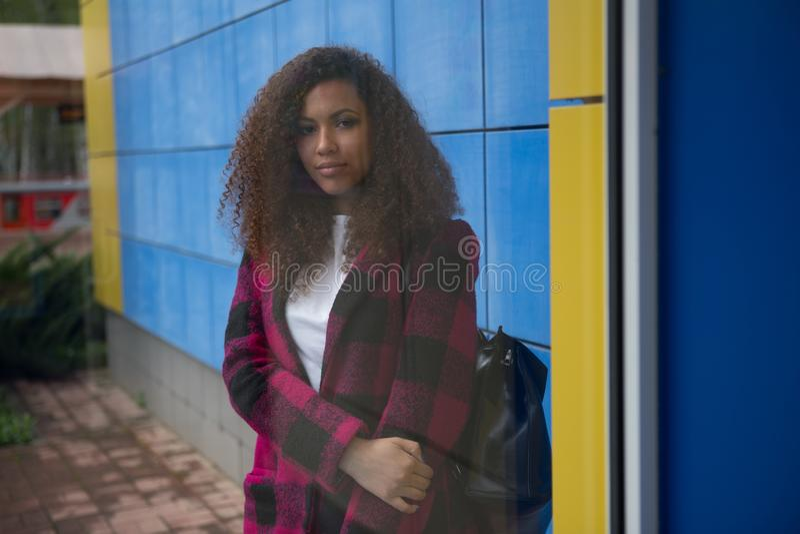 Väder för höst för ledsen flicka för höst utomhus-, stående av en ung vuxen flicka i ett lag i en bur, skotsk stil arkivbild