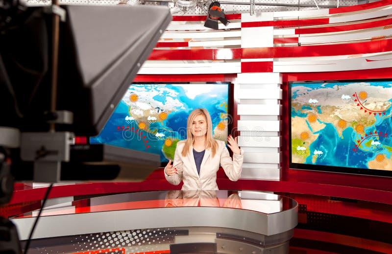 Väder förutser a-televisionanchorwomanen på studion arkivbild