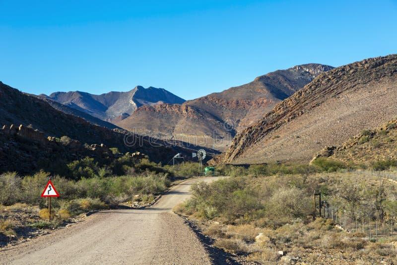 Väderkvarn bredvid grusvägen framme av berget royaltyfria foton